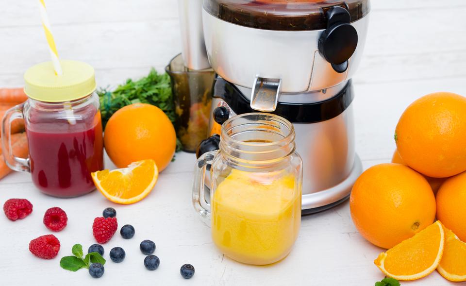 Un blender cu două pahare de suc și diferite fructe pe o masă.