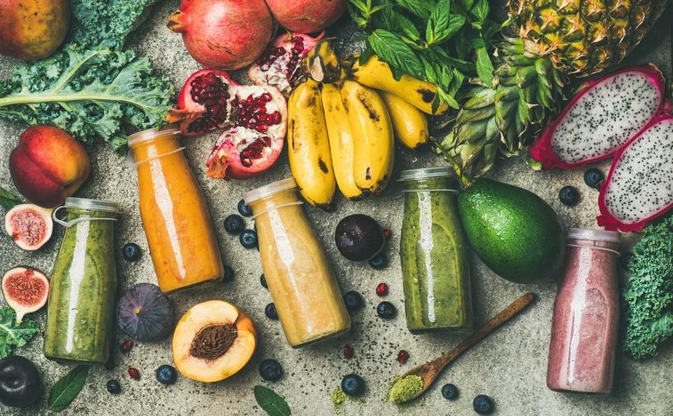 Sticle cu sucuri și diferite alimente pe un blat de bucătărie.