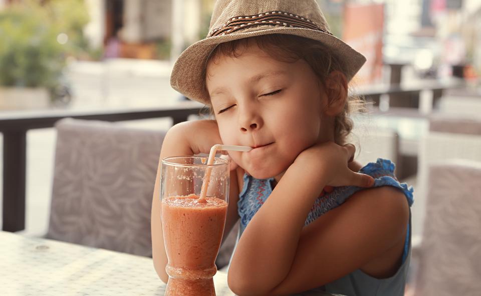 Fetiță cu pălărie sorbind un smoothie.