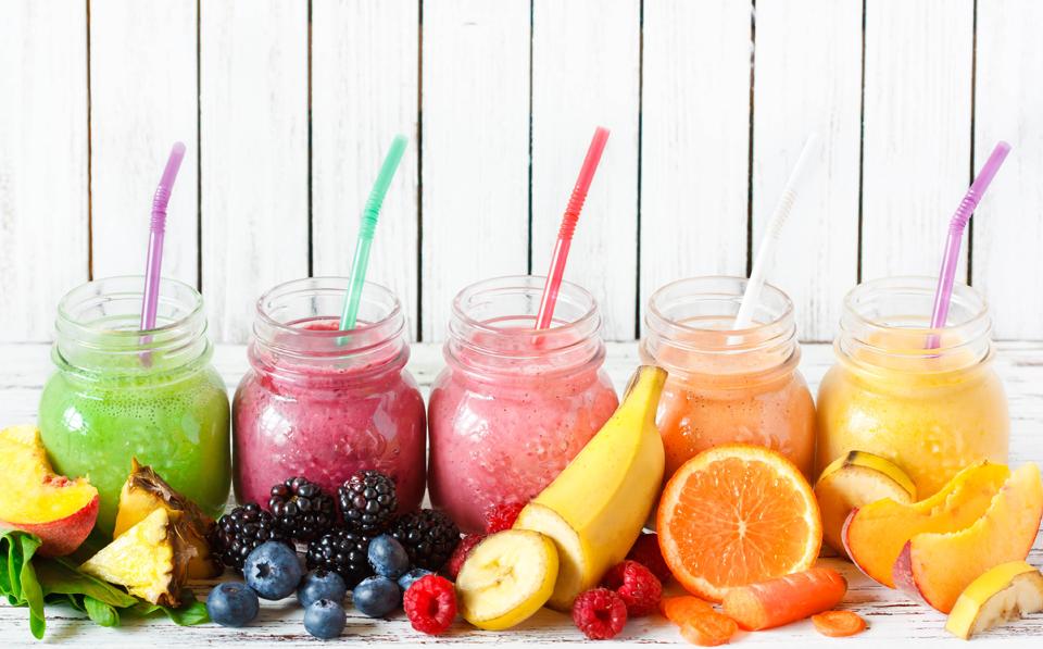 Cinci pahare cu diferite tipuri de sucuri din fructe.