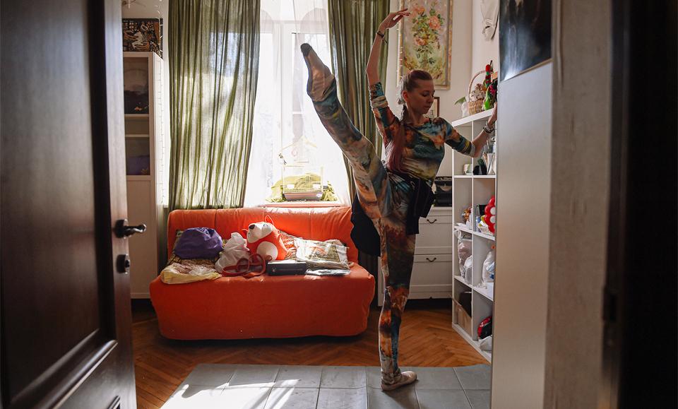 Fata exersand miscari de balet intr-o camera.