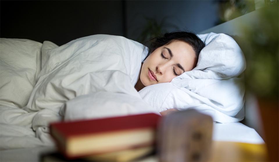 Fata dormind intr-un pat.