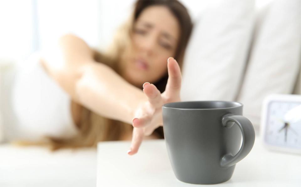 Fata incercand sa ajunga la o cana cu cafea.