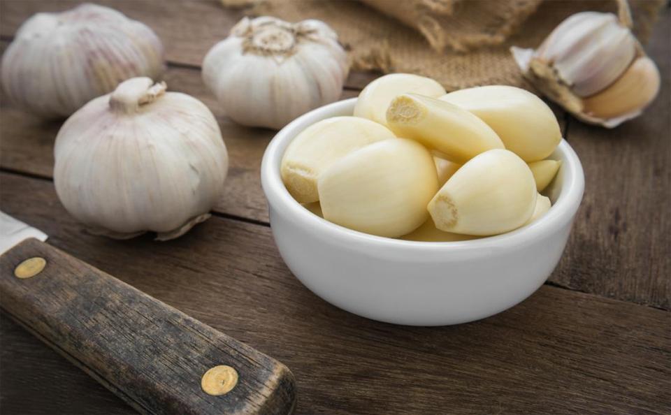 Catei de usturoi curatati intr-un bol langa alte capatani de usturoi si un cutit.