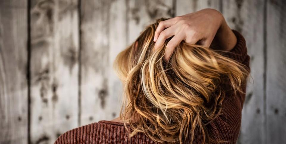 Femeie blonda cu mana in par vazut din spate.