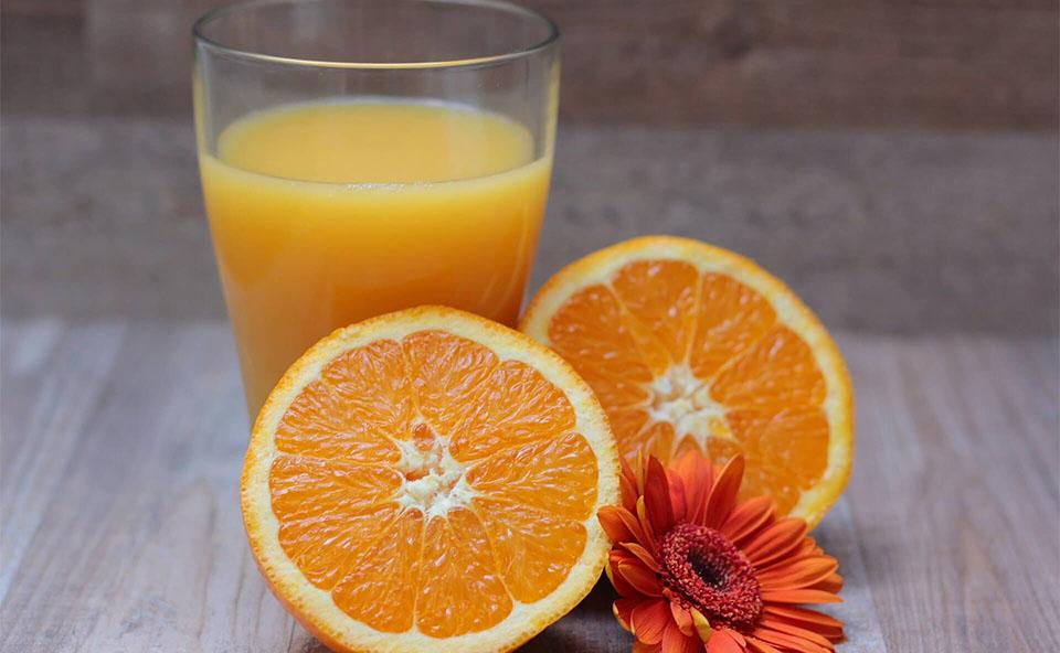 O portocala taiata in doua langa o floare si un pahar cu suc.