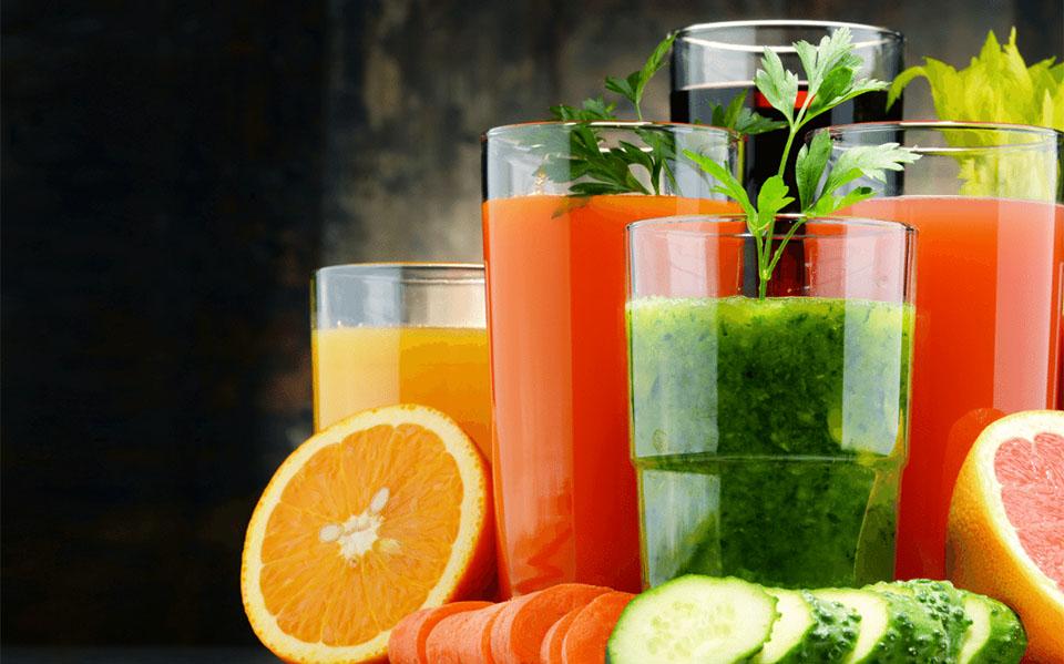 Diverse fructe si legume langa pahare cu sucuri.