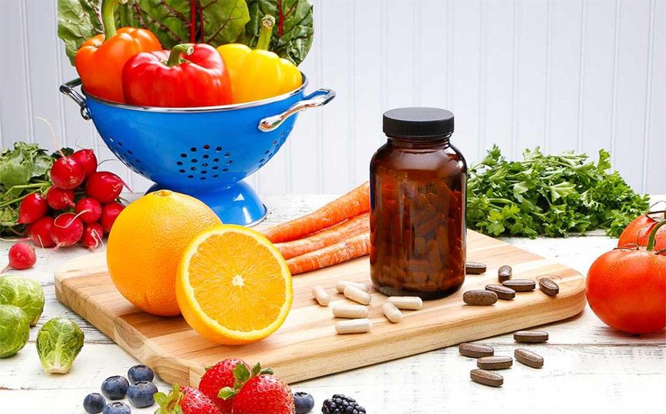 Flacon cu pastile pe o masa cu fructe si legume.