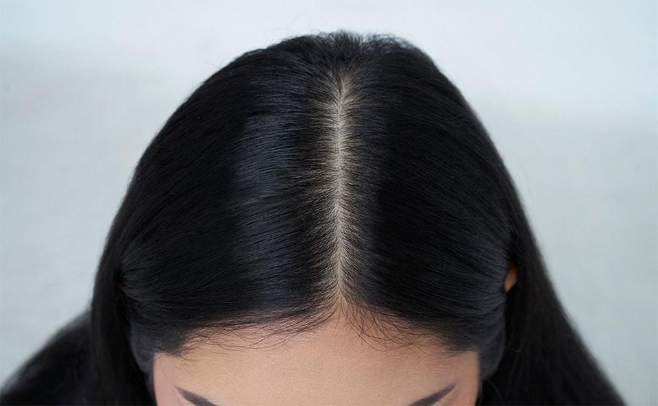 Capul unei fete cu parul negru vazut de sus.