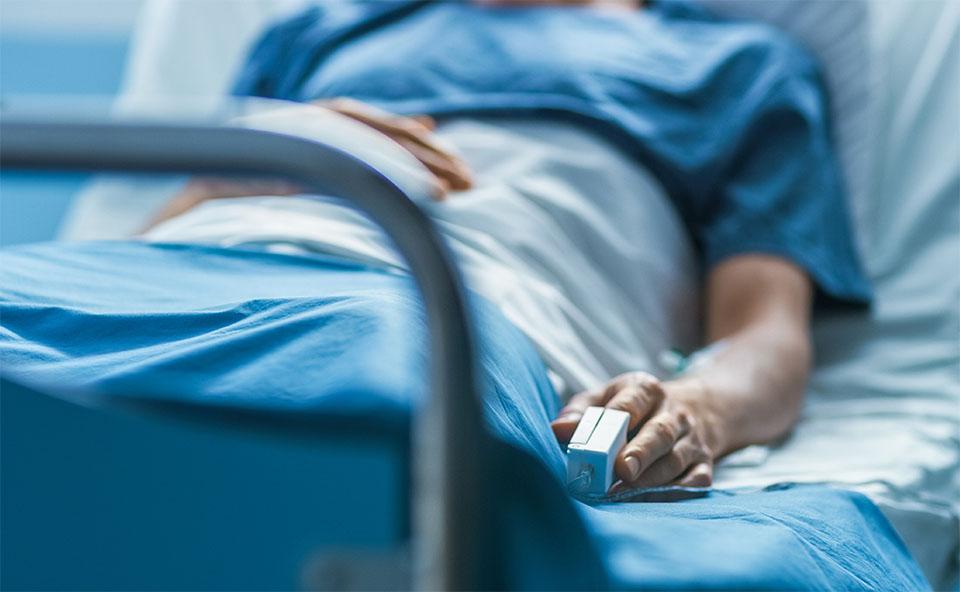 Persoana stand intr-un pat de spital.