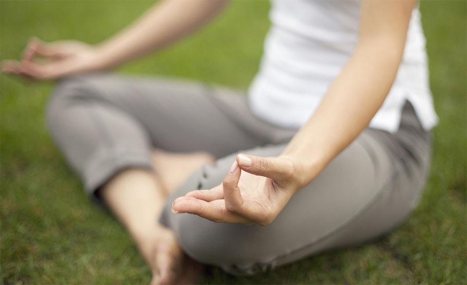 Persoana facand yoga in iarba.