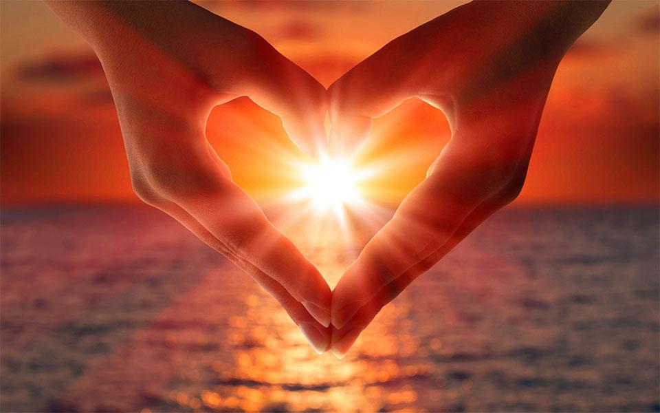 Doua maini facand o inima in jurul soarelui.