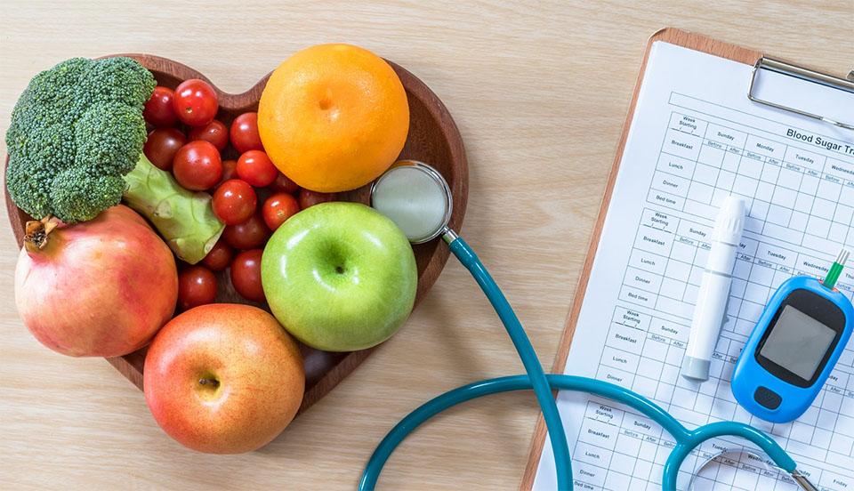 Fructe si legume intr-un castron in forma de inima langa un stetoscop si un glucometru.