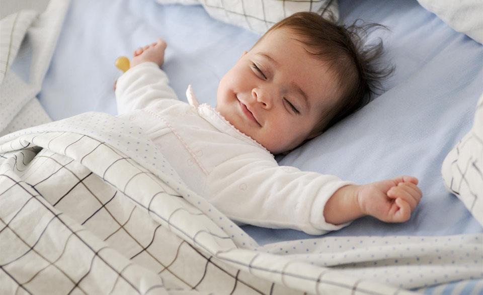 Bebelus dormind cu mainile deschise.