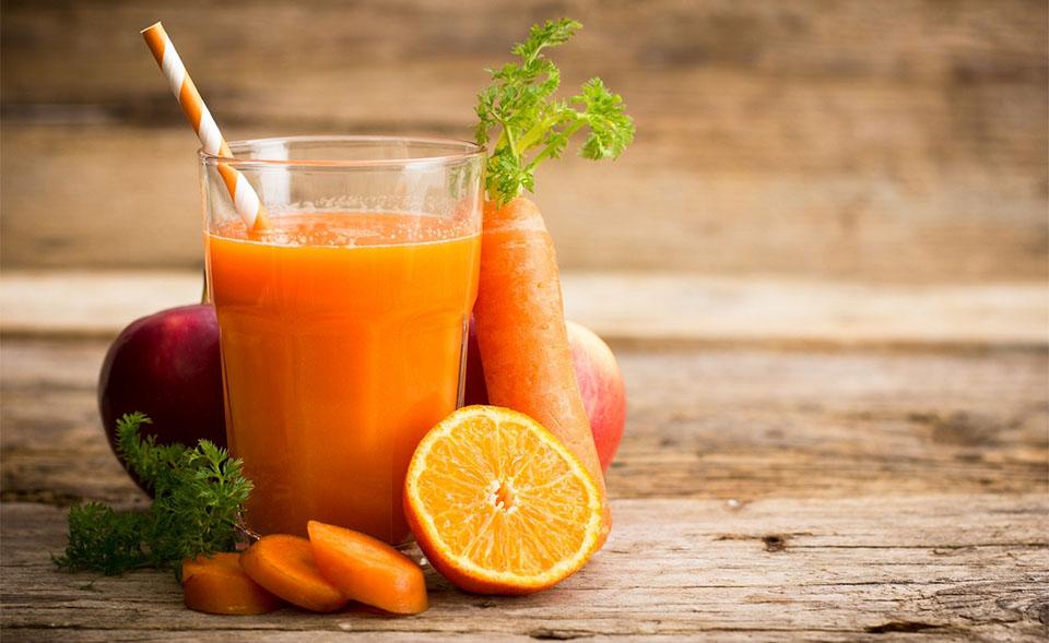 Pahar cu suc cu morcovi langa diverse fructe si legume.