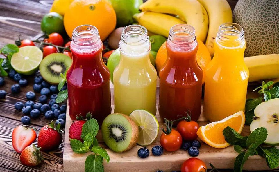 Patru sticle cu sucuri diferite langa diferite fructe si legume.