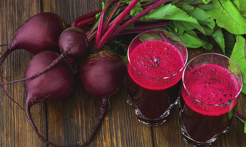 Doua pahare cu suc de sfecla rosie si o legatura de sfecla rosie pe o masa.