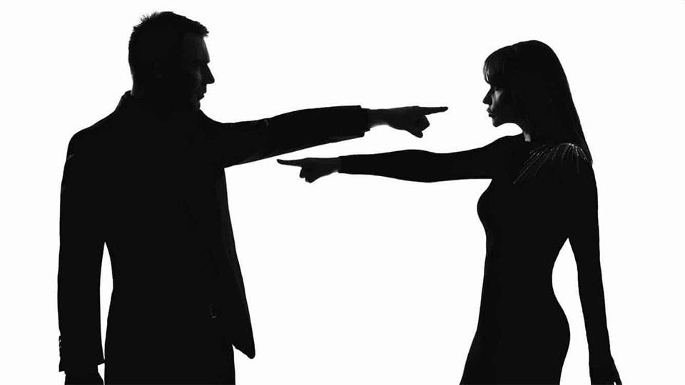 Siluetele unui barbat si a unei femei certandu-se.