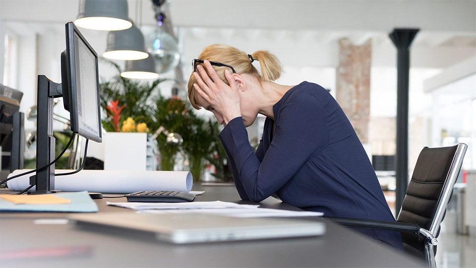 Fata blonda tinandu-se cu mainile de cap la un birou.