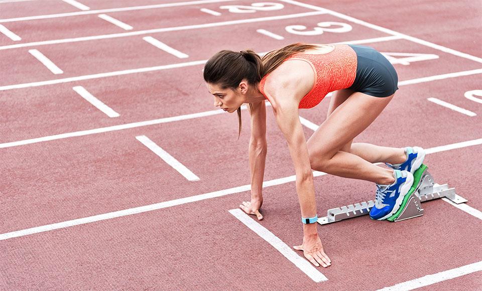 Fata pregatindu-se sa ia startul pe o pista de alergare.