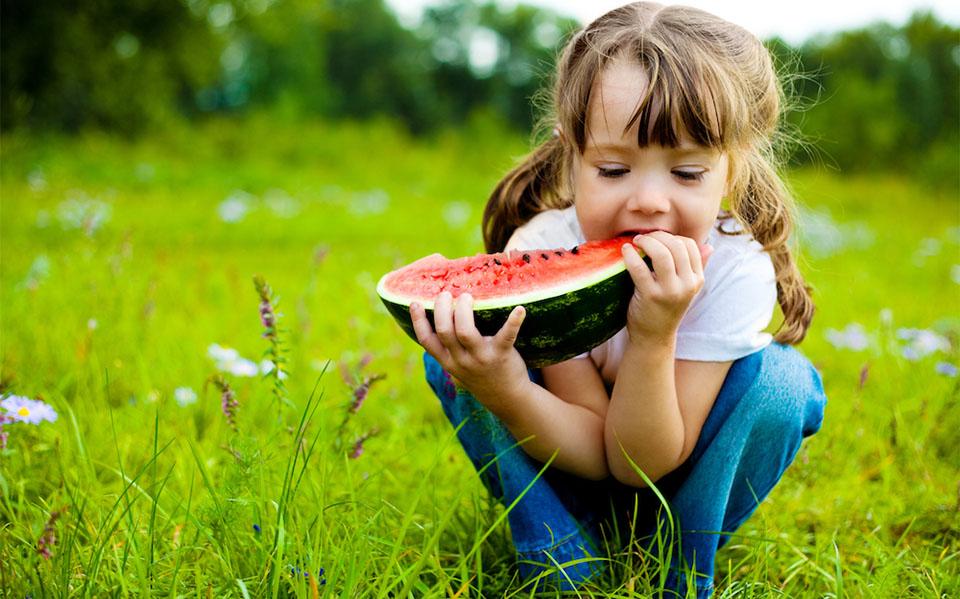 Fata mancand o felie de pepene in iarba