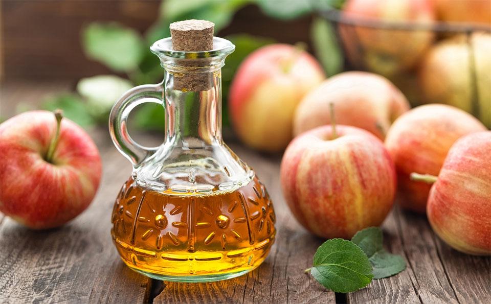 Sticla cu otet de mere langa o gramada de mere.