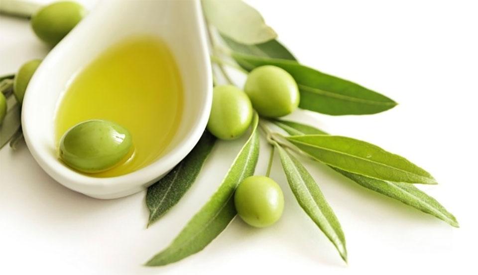 Masline cu fructe si frunze langa o lingura cu ulei.