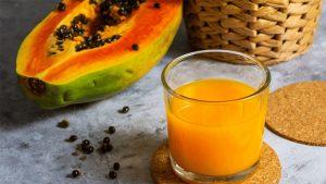 Papaya taiat si un pahar cu suc pe o masa.