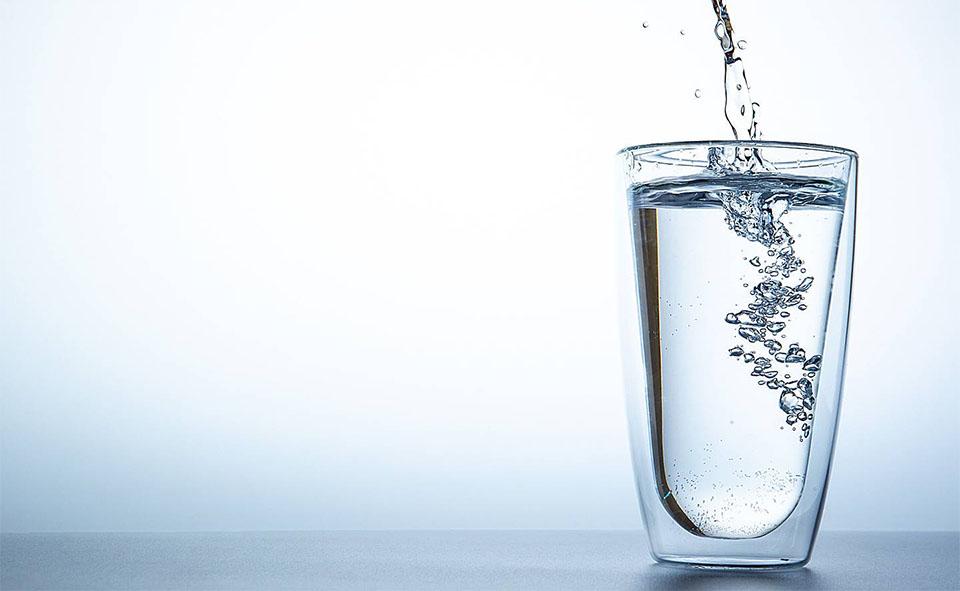 Apa curgand intr-un pahar.
