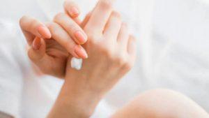 Fata dandu-si cu crema pe maini.