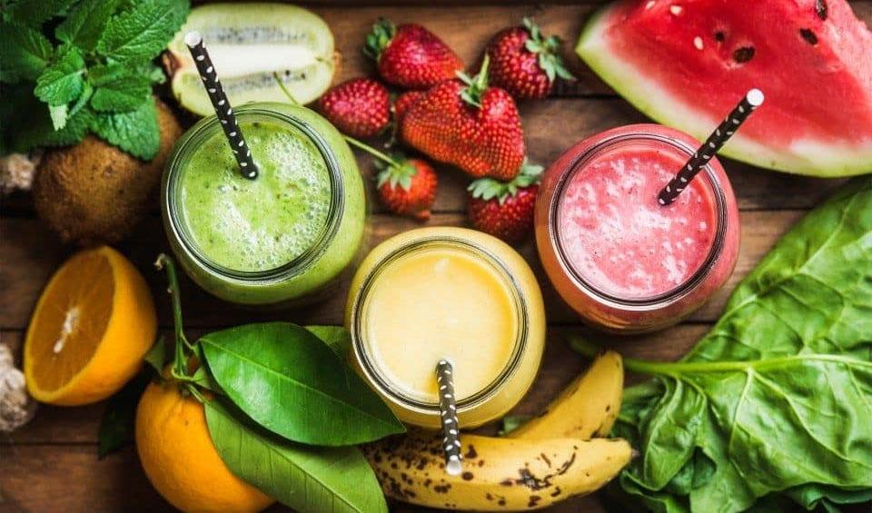 Pahare cu sucuri langa diferite fructe.