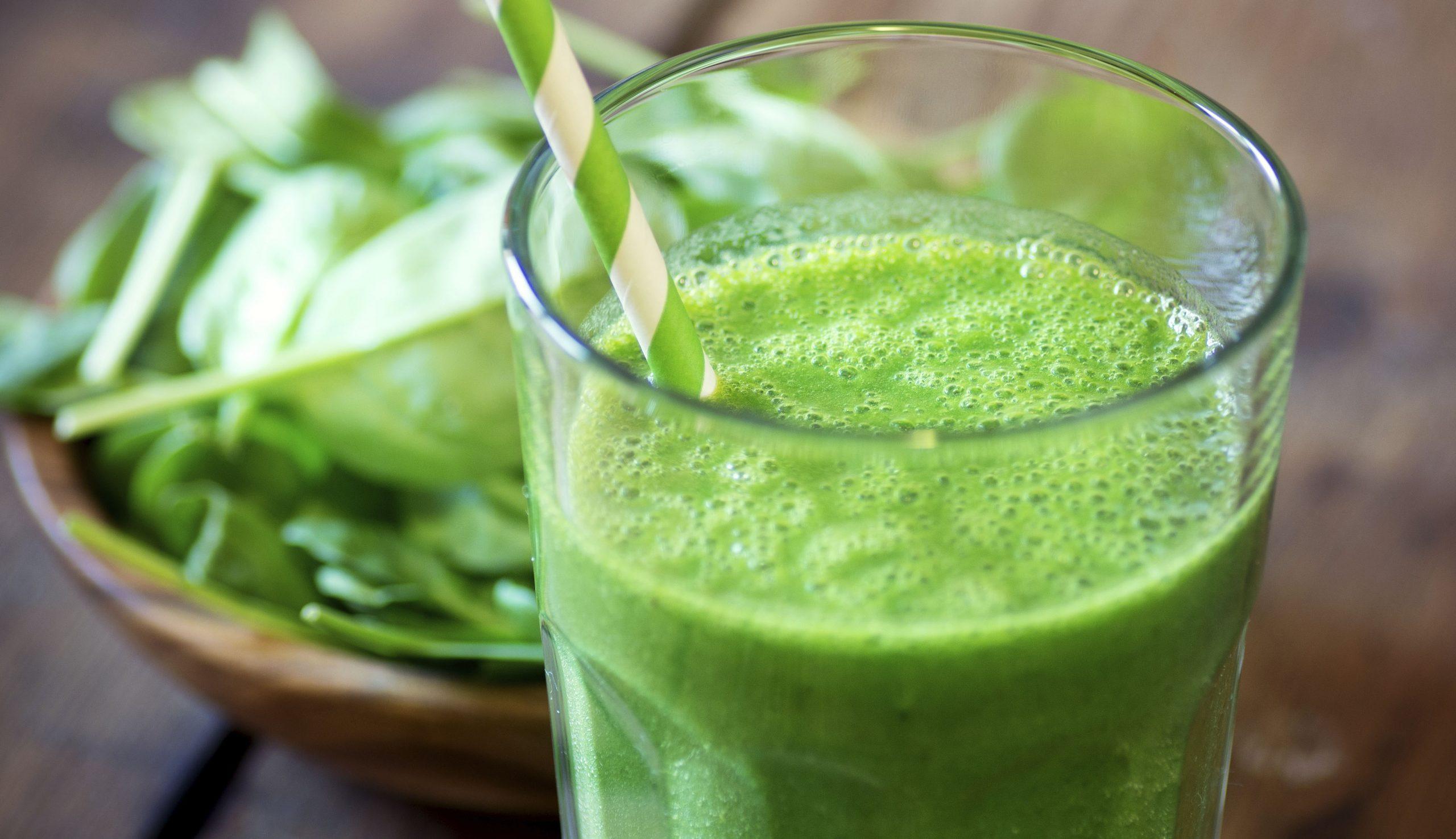 Pahar cu suc verde si un castron cu frunze verzi.