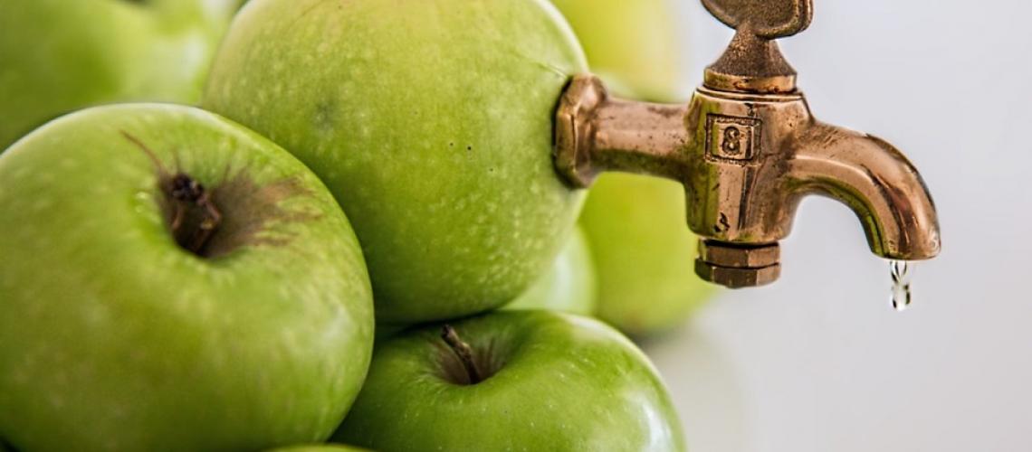 Un robinet băgat într-un măr verde.